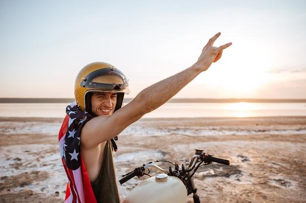 Sorridente uomo brutale in casco d'oro e mantello bandiera americana seduto sulla sua moto con le mani in aria