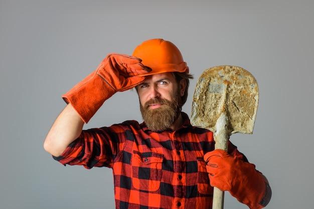 Il costruttore sorridente in elmetto con l'operaio della pala con il costruttore di vanga in guanti da lavoro tiene la vanga