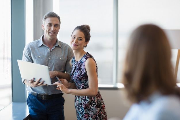 Colleghi di affari sorridenti che discutono sopra il computer portatile