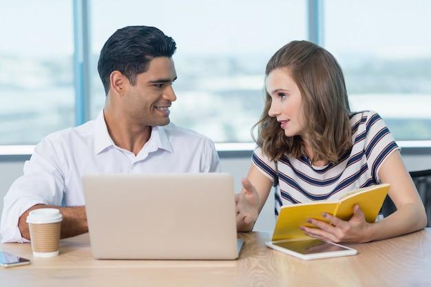Sorridenti colleghi di lavoro che interagiscono tra loro durante l'utilizzo di laptop