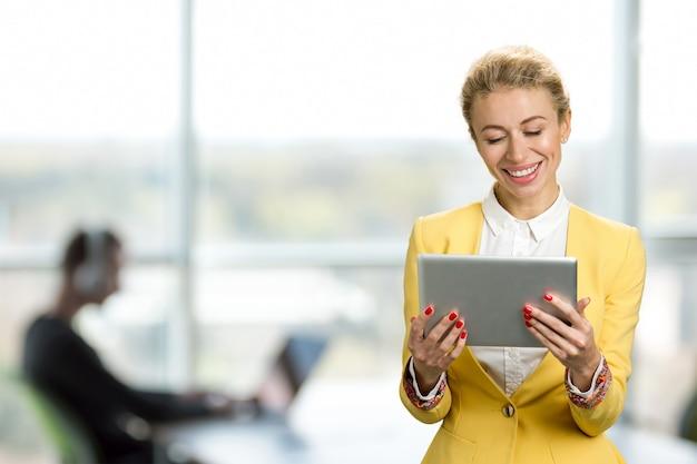 Signora sorridente di affari con il ridurre in pani del pc. allegro giovane donna d'affari alla ricerca su tablet computer e sorridente, finestra dell'ufficio.