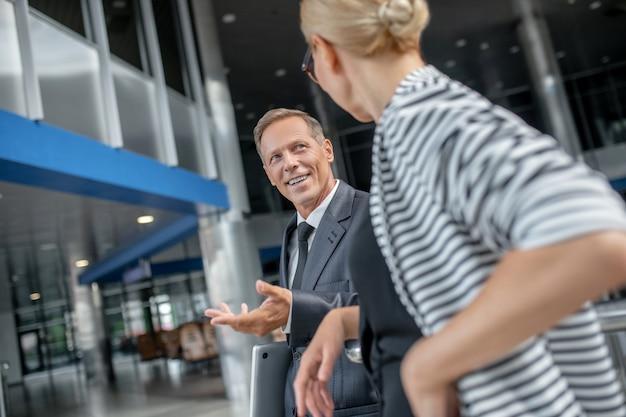 Uomo d'affari sorridente che gesturing e collega di sesso femminile