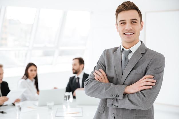 Uomo d'affari sorridente in piedi con le braccia incrociate in ufficio con i colleghi al tavolo by