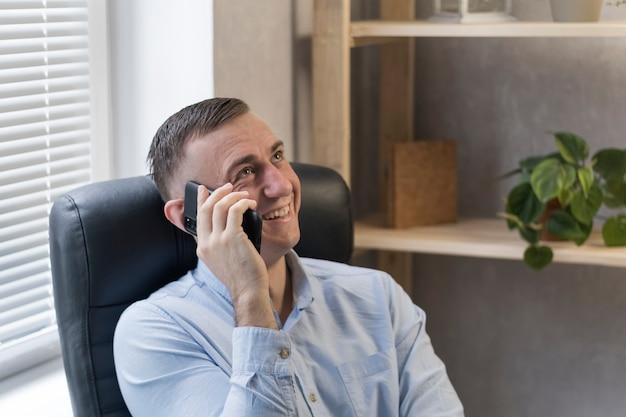 Uomo d'affari sorridente parlando al telefono nel suo ufficio e sorridente. giovane regista maschio con il telefono in mano.
