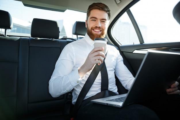 Uomo sorridente di affari con il computer portatile che tiene tazza di caffè