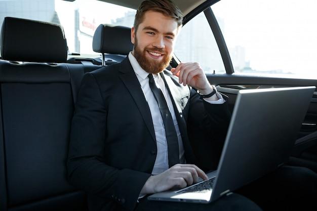 Uomo d'affari sorridente con il portatile