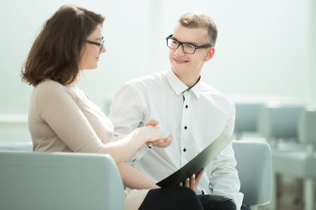 Soci d'affari sorridenti che si stringono la mano mentre sono seduti in ufficio. concetto di cooperazione