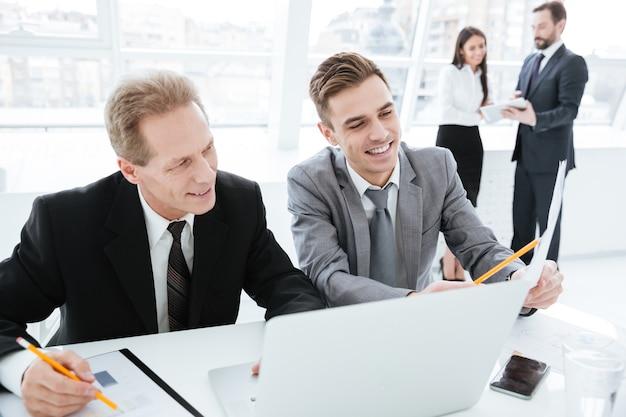 Partner commerciali sorridenti seduti al tavolo con laptop e documenti in ufficio con i colleghi