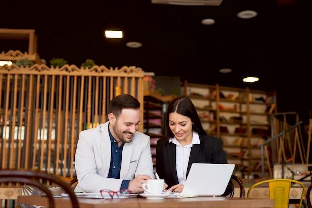 Gente di affari sorridente che ha riunione nel self-service.