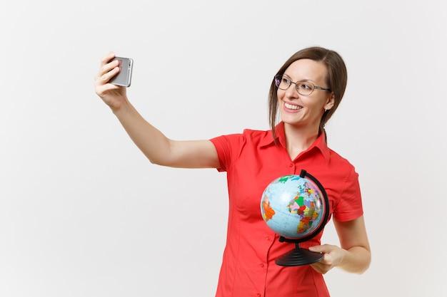 Donna sorridente dell'insegnante di affari in camicia rossa che tiene telefono cellulare e che fa prendendo selfie sparato con il globo isolato su fondo bianco. insegnamento dell'istruzione nel concetto di università delle scuole superiori. copia spazio.