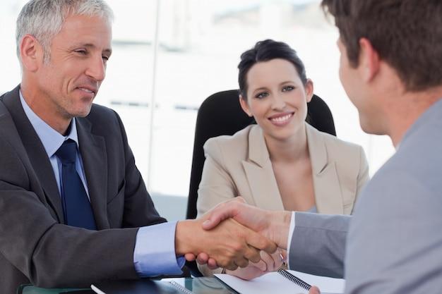 Squadra sorridente di affari che conclude un accordo con un cliente