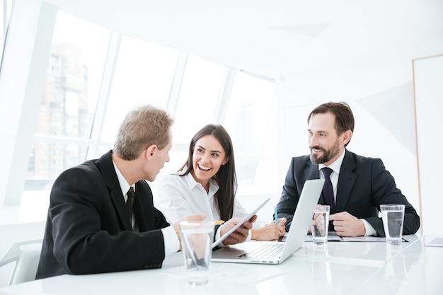 Sorridente team aziendale seduto al tavolo con laptop e tablet in conferenza in ufficio