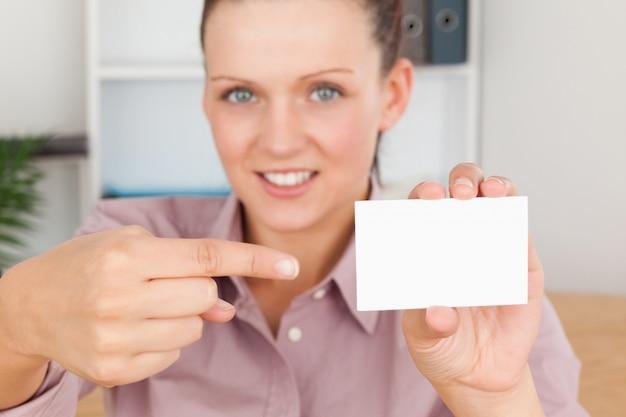 Sorridente donna d'affari che punta a una carta