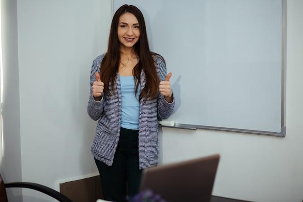 Donna sorridente di affari che indica dito sullo spazio della copia. abito stile business. giovane modella con i capelli lunghi.