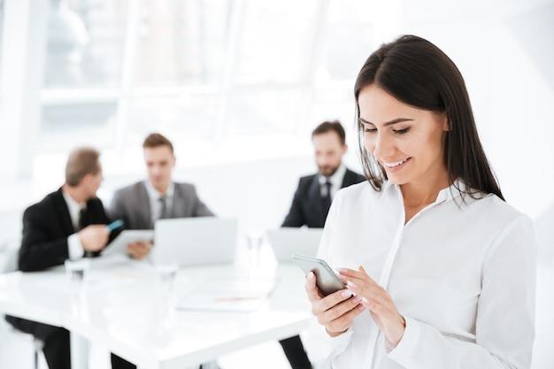 Donna d'affari sorridente che usa il cellulare con i colleghi in ufficio