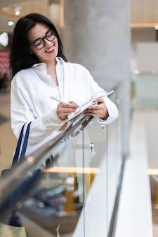 Sorridente donna d'affari che scrive elenco di carta che prende appunti al centro commerciale con emozioni positive positive