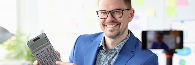 Blogger sorridente dell'uomo d'affari che tiene calcolatrice nelle sue mani concetto di guadagni a distanza
