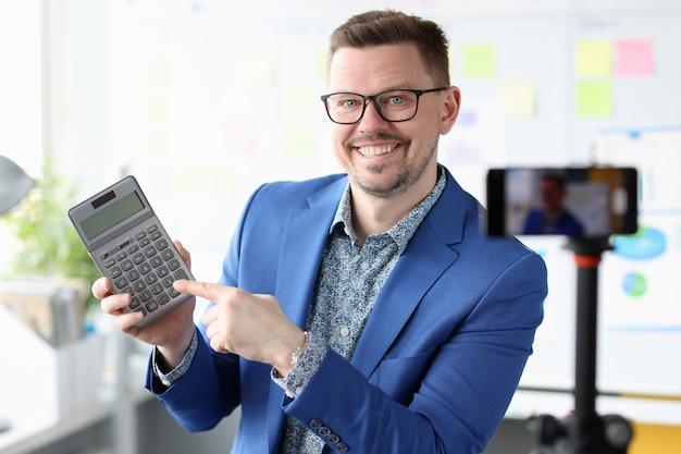 Sorridente imprenditore blogger tenendo la calcolatrice nelle sue mani