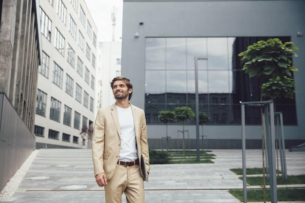 Uomo d'affari sorridente in vestito convenzionale che tiene laptop senza fili sull'aria fresca. uomo barbuto felice che utilizza computer portatile per lavoro