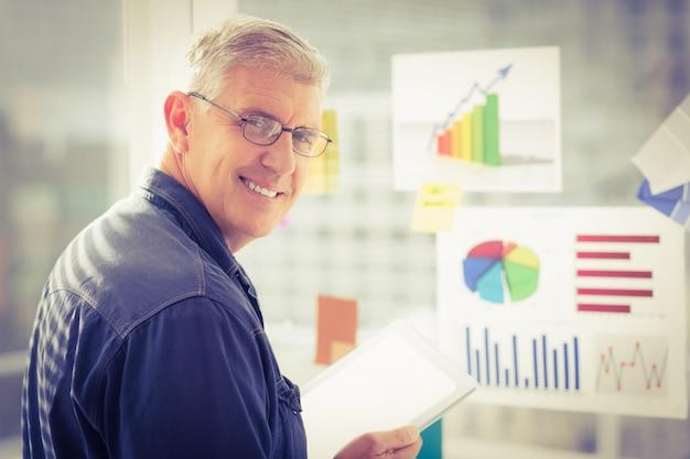 Uomo d'affari sorridente che tiene una compressa digitale
