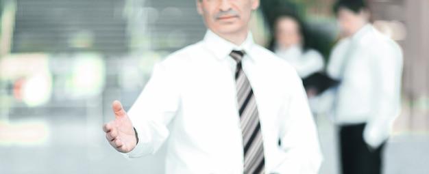Sorridente uomo d'affari tendendo la mano per il saluto. il concetto di cooperazione.