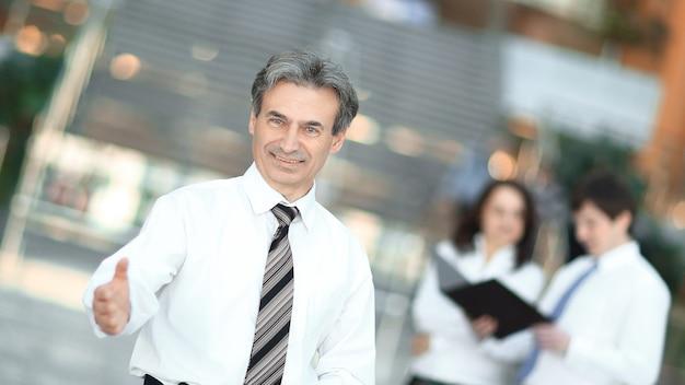 Uomo d'affari sorridente che tende la mano per salutare. il concetto di cooperazione.