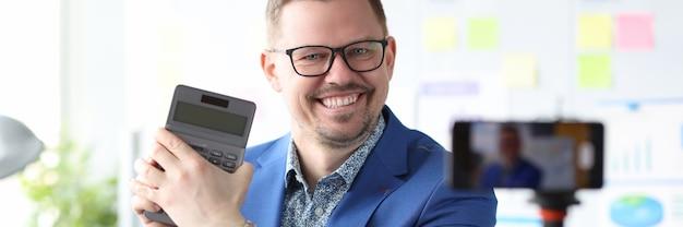 L'uomo d'affari sorridente tiene la calcolatrice e conduce corsi online su come aumentare i profitti