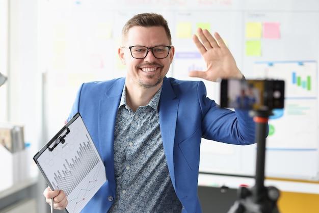 Uomo d'affari sorridente tiene appunti finanziari nelle sue mani e registra video sul telecomando della fotocamera