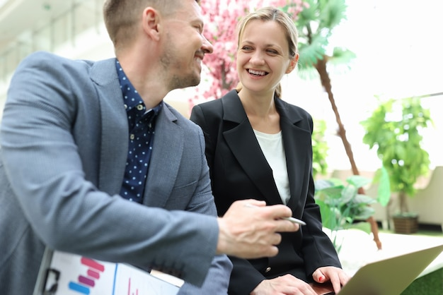 L'uomo d'affari sorridente sta discutendo il progetto di affari con la donna d'affari