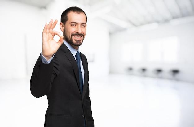L'uomo d'affari sorridente che fa bene firma dentro una stanza luminosa