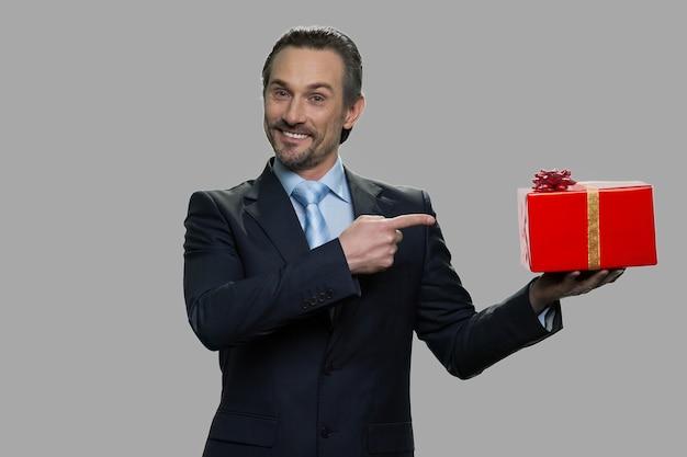 Uomo d'affari sorridente che indica al contenitore di regalo nella sua mano. offerta speciale per le vacanze.