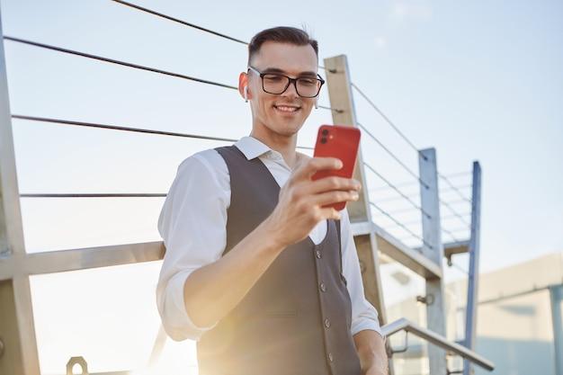 Uomo d'affari sorridente che legge un messaggio sul suo smartphone.