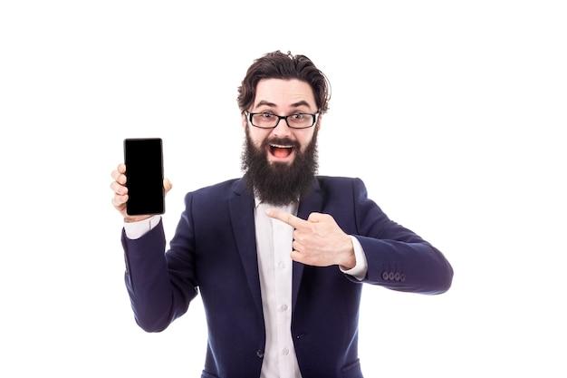 Uomo d'affari sorridente che mostra lo schermo in bianco dello smartphone e che punta su di esso, isolato su sfondo bianco