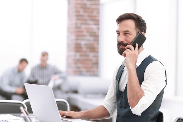 Imprenditore sorridente seduto alla sua scrivania in office.people e tecnologia
