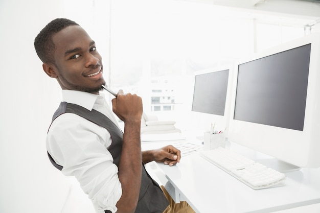Uomo d'affari sorridente che si siede e che tiene matita