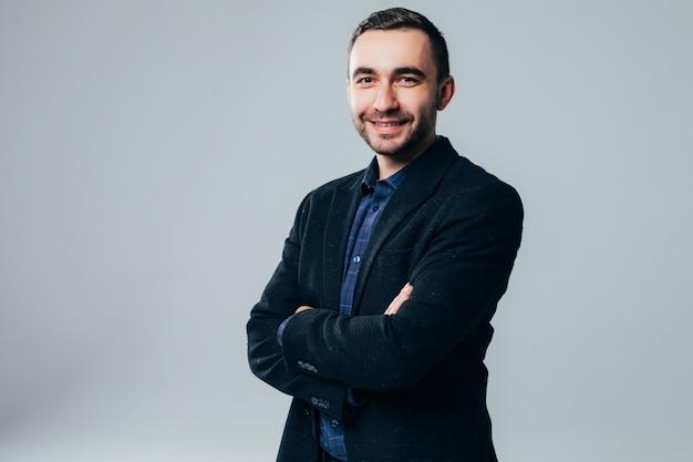 Uomo d'affari sorridente in piedi con le braccia piegate isolato su uno sfondo bianco
