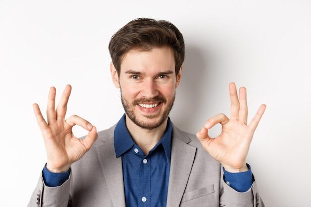 Uomo d'affari sorridente in vestito che mostra segni di approvazione, garanzia di prodotto di qualità, lode buona cosa, in piedi su sfondo bianco