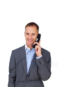 Sorridente uomo d'affari aggrovigliato nei fili del telefono