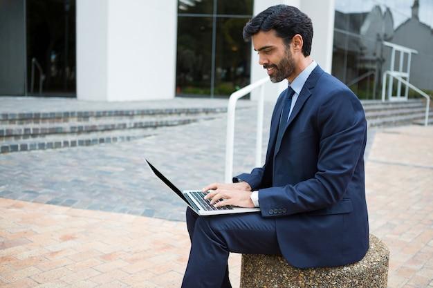 Uomo d'affari sorridente che per mezzo del computer portatile nei locali dell'ufficio
