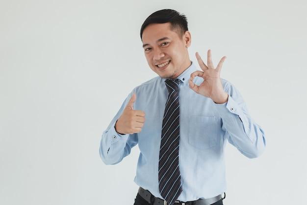 Sorridente uomo d'affari che indossa camicia blu e cravatta in posa con il pollice in alto e gesticolando bene su sfondo bianco