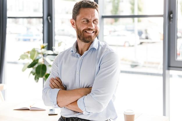 Uomo d'affari sorridente con le braccia piegate