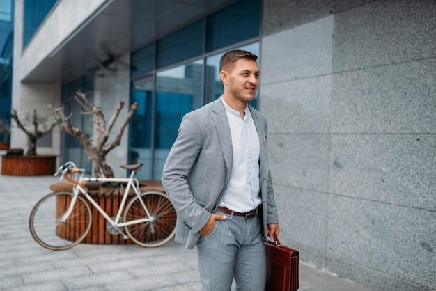 Uomo d'affari sorridente con la bicicletta presso l'edificio per uffici di vetro nel centro cittadino. persona di affari che guida sul trasporto ecologico sulla strada della città, in stile urbano