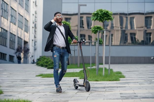 Uomo d'affari sorridente con scooter elettrico in piedi vicino al moderno edificio aziendale parlando al telefono