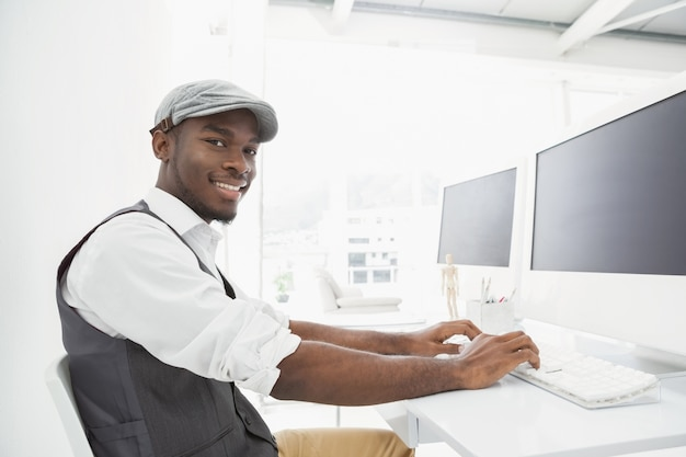 Uomo d'affari sorridente con il cappello che scrive sulla tastiera