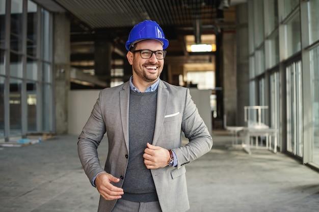 Uomo d'affari sorridente con il casco sulla testa in piedi nell'edificio nel processo di costruzione e il controllo sui lavori