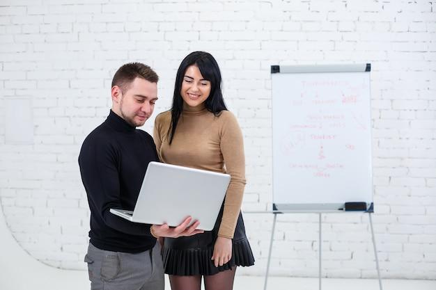 Sorridente uomo d'affari e donna manager sono in piedi con il computer portatile e guardando lo schermo. stare su uno sfondo bianco.