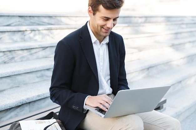 Uomo d'affari sorridente che lavora al computer portatile all'aperto