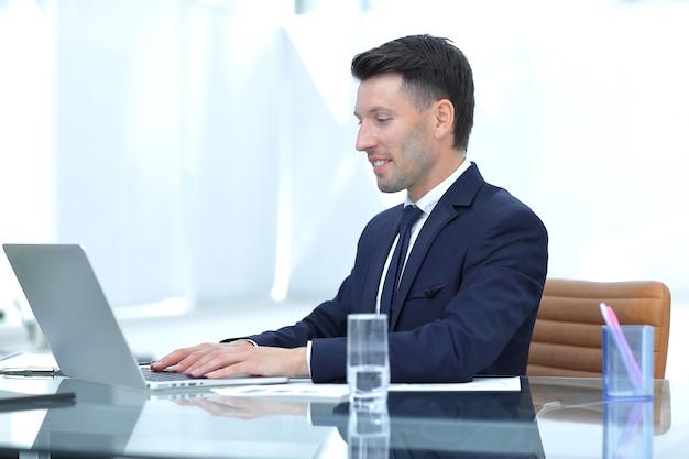 Uomo d'affari sorridente che lavora al computer portatile