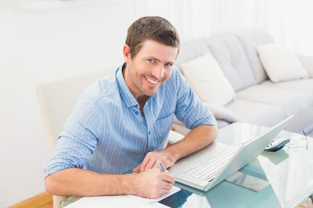 Scrittura sorridente dell'uomo d'affari al suo scrittorio