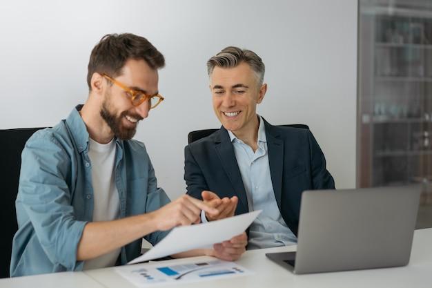 Sorridente imprenditori utilizzando laptop, parlando, comunicazione, lavoro in ufficio. due colleghi di lavoro in riunione